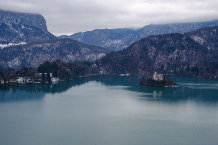 View of Church Amidst Lake and Mountains Tranquil Scene Architecture Mountain Water Scenics - Nature Beauty In Nature Mountain Range Cloud - Sky Waterfront Reflection Tranquility Nature Sky Travel Photography Church Lake Bled Slovenia Beauty Blue No People Outdoors Landscape