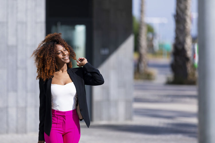 Front view of young beautiful curly woman wearing elegant clothes and handbag while standing in the street in sunny day Curly Hair Hairstyle One Person City Young Adult Three Quarter Length Real People Architecture Focus On Foreground Young Women Standing Hair Front View Lifestyles Women Holding Day Adult Building Exterior Beautiful Woman Outdoors Standing Posing Model Handbag  Afro African American Smiling Laughing Looking At Camera Looking Away Elegant Attractive Bussinesswoman Empowered City Life Urban Walking Beautiful Pink