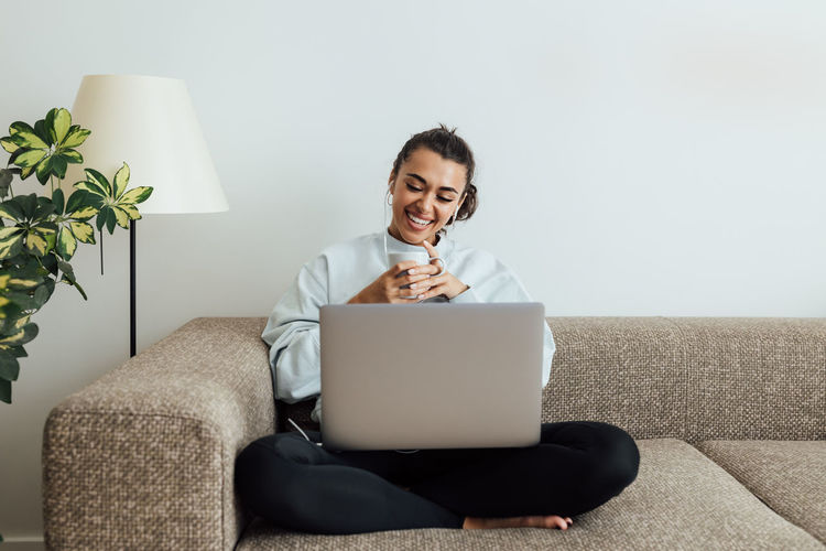 Smiling young woman using phone while sitting on sofa