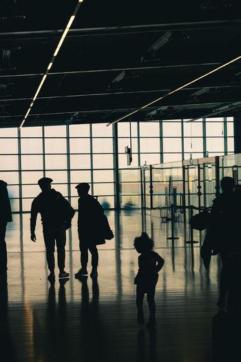 Silhouette people walking on railroad station platform