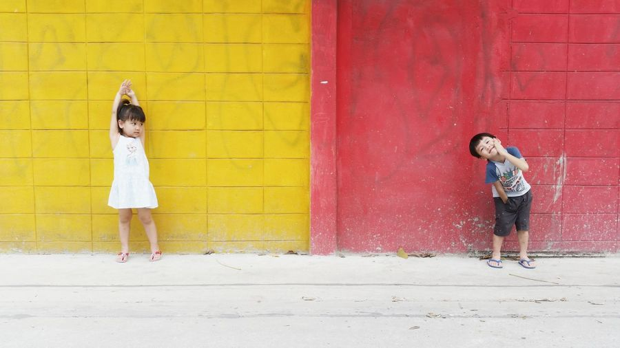 Full length of smiling girl playing in the wall