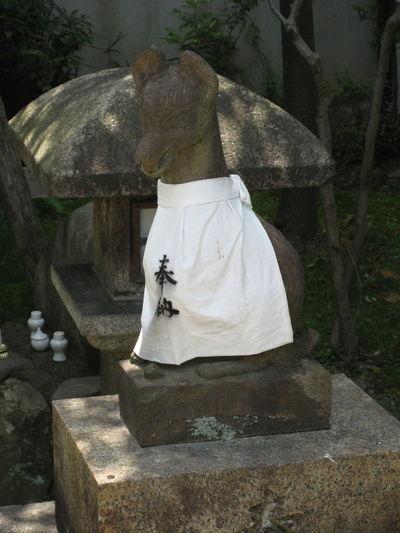 A fox spirit wearing a white bib at a Japanese shinto shrine in Kyoto, Japan. Japan Japanese Shinto Shrine Japanese Shrine Shinto Shrine Shrine Shrine Of Japan Spirit Animal Animal Spirits Deity Fox Harvest Inari Kyoto Messenger Religion Sculpture Spirituality Statue
