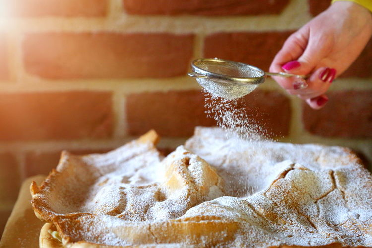 Cropped hand of woman dusting powdered sugar on pie