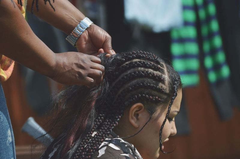 Hairdresser braiding hair of woman