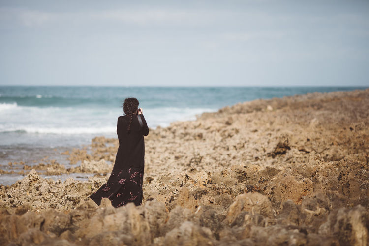Rear View Of Woman Photographing On Beach