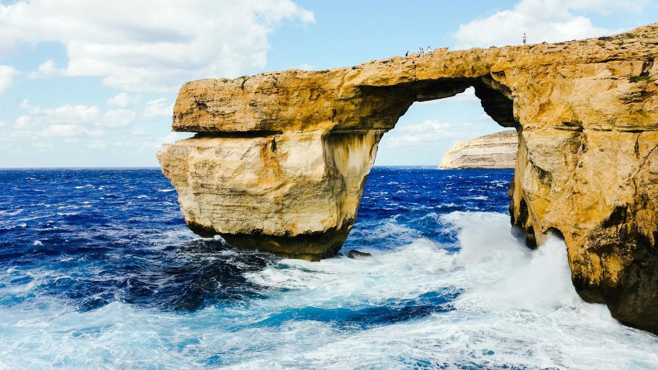 sea, nature, beauty in nature, rock formation, rock - object, sky, natural arch, scenics, water, horizon over water, tranquility, non-urban scene, tranquil scene, day, cloud - sky, no people, waterfront, outdoors, physical geography, power in nature, wave