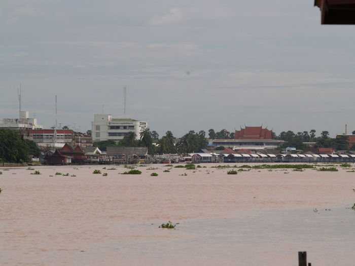 Scenic view of river by buildings against sky