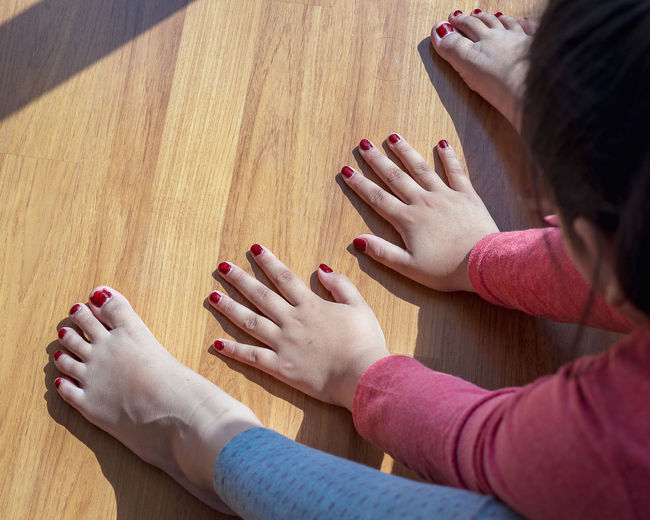 High angle view of hands and woman lying on floor
