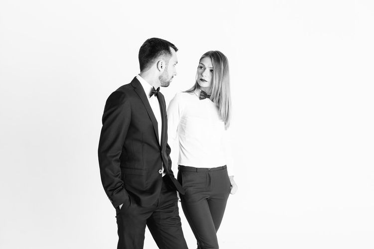 Elegant couple looking at each other while standing against white background