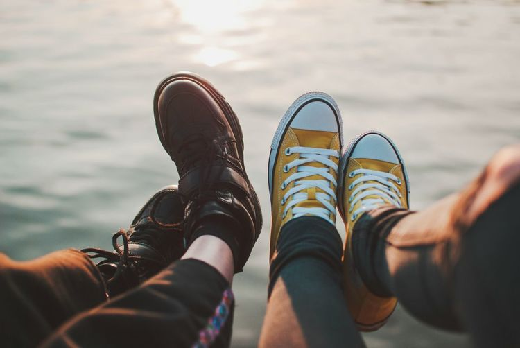 Low section of couple in shoes at sea