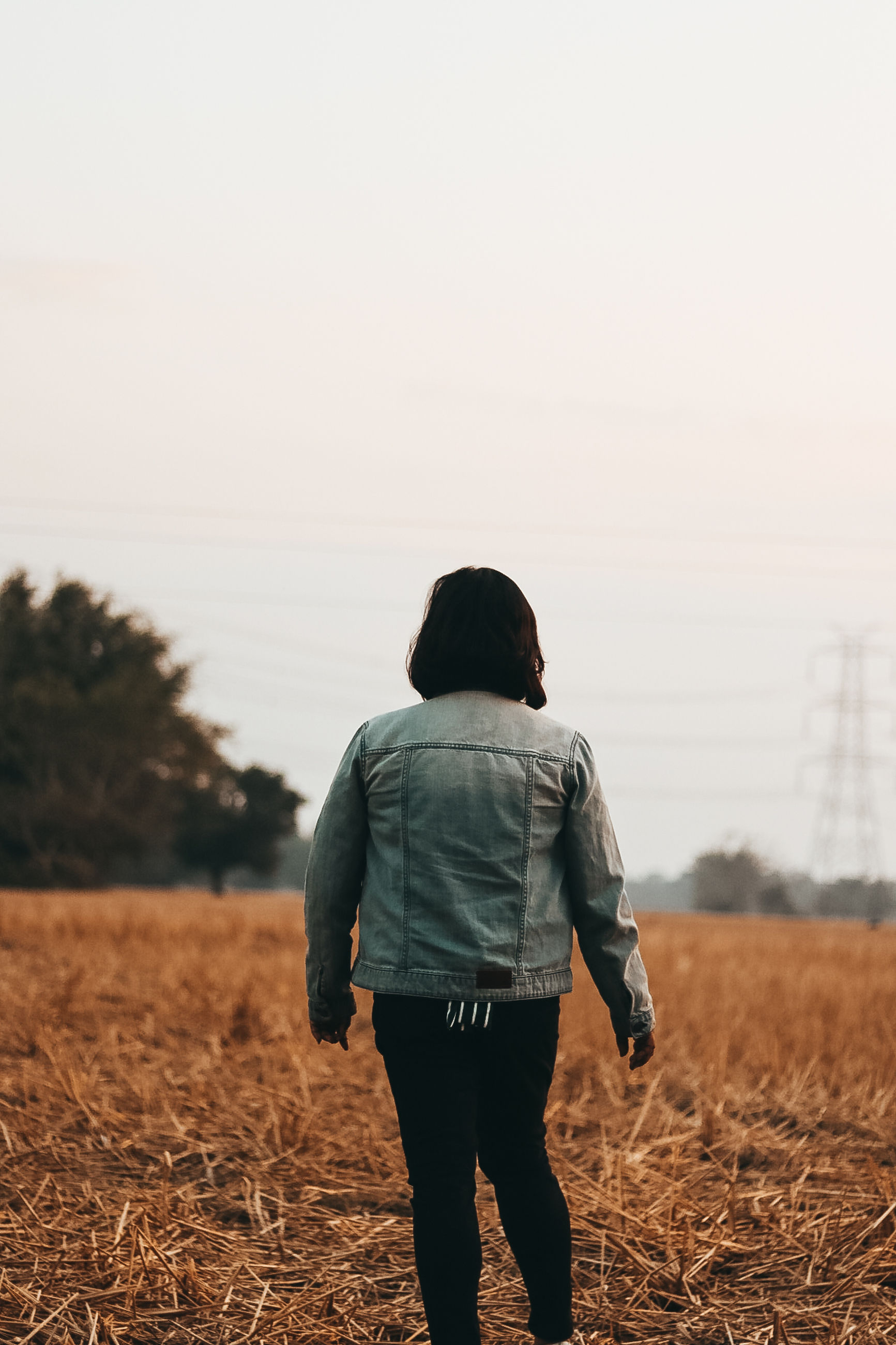 rear view, sky, one person, field, real people, land, lifestyles, leisure activity, nature, standing, casual clothing, three quarter length, clear sky, landscape, adult, women, environment, focus on foreground, walking, hairstyle, outdoors