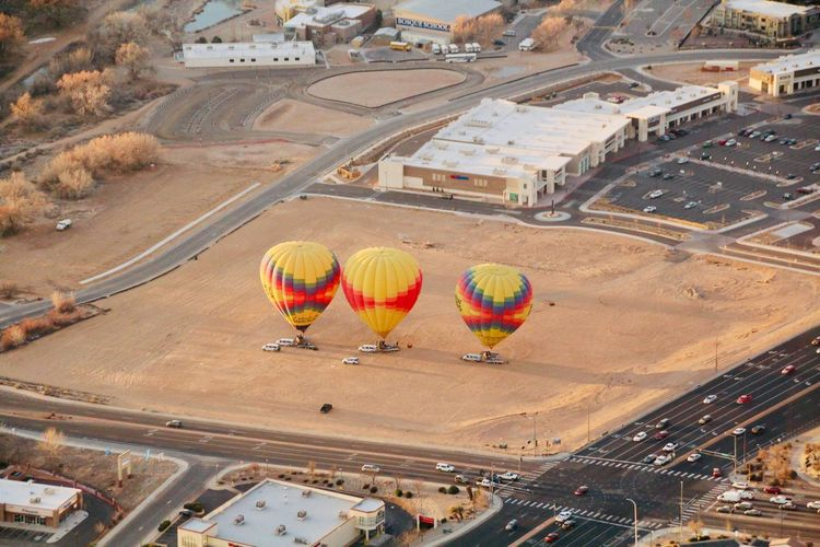 High angle view of hot air balloon flying over city