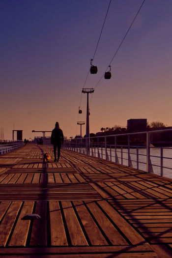 Rear view of man walking on railroad tracks against sky during sunset