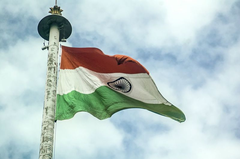 Low angle view of indian flag waving against cloudy sky