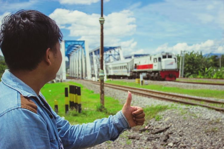 Rear view of man with train at railroad tracks against sky
