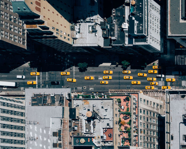 Directly above view of cars on street amidst buildings in manhattan