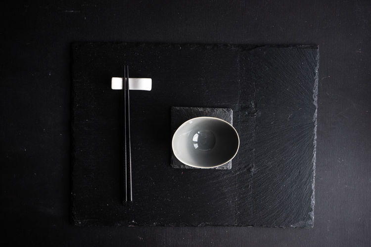 Directly above shot of bowl and chopsticks on black table