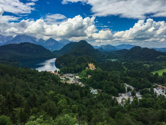 Scenic view of hohenschwangau castle by alpsee amidst trees against sky
