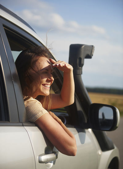 Smiling young woman looking at view during road trip Car Passenger Woman Travel Road Trip Vacation Summer Journey Adventure Look At View Look Window Trip Transportation Travel Destinations Young Woman Adult People Indoors  City City Life Taxi Service Beautiful Woman One Woman Only Only Women Carefree Freedom Sunglasses Tourist Tourism Real People Fun Drive Van Females Happiness Joy Smiling Toothy Smile