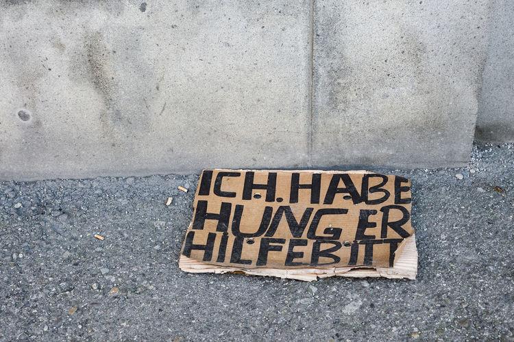 Hungry, please help (ich habe hunger hilfebitt) written on brown cardboard seen in Marienplatz, Munich. Helping Hungry Sign Social Close-up Communication Day Help Hilfebitt Hunger No People Outdoors Social Issues Street Text