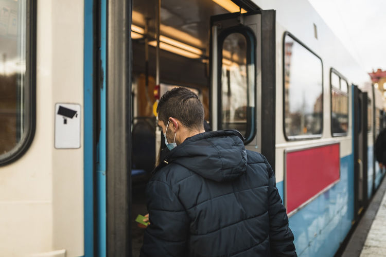 Rear view of man standing on train window