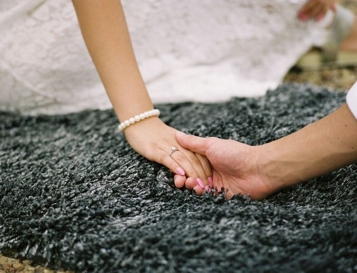 Cropped image of bridegroom holding hand of bride on carpet