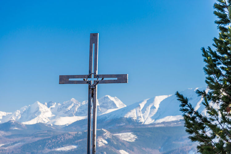 Cross against snowcapped mountains