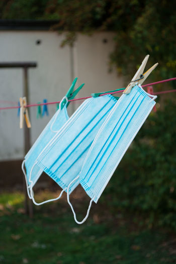 Close-up of medical face masks drying on clothesline