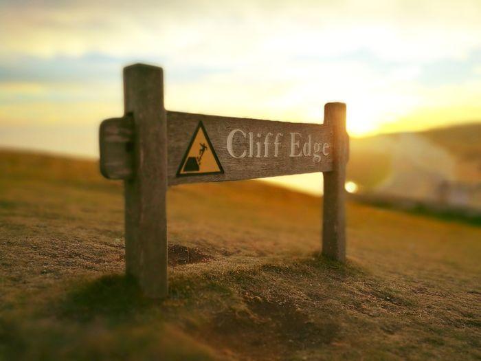 Close-up of sign on landscape against sky
