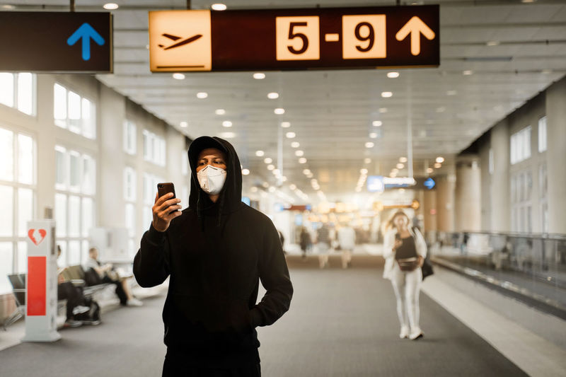 Man with mask using mobile phone at airport