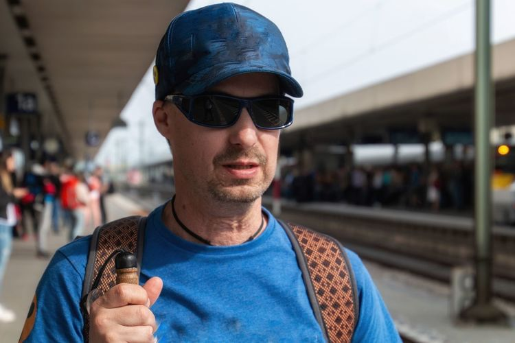 Man wearing sunglasses at railroad station platform