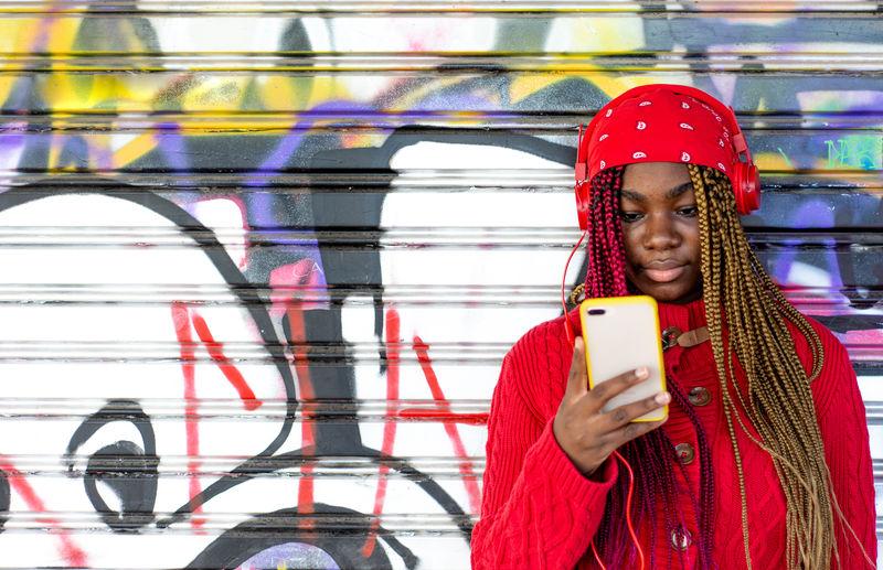 Portrait of senior man holding mobile phone standing against graffiti