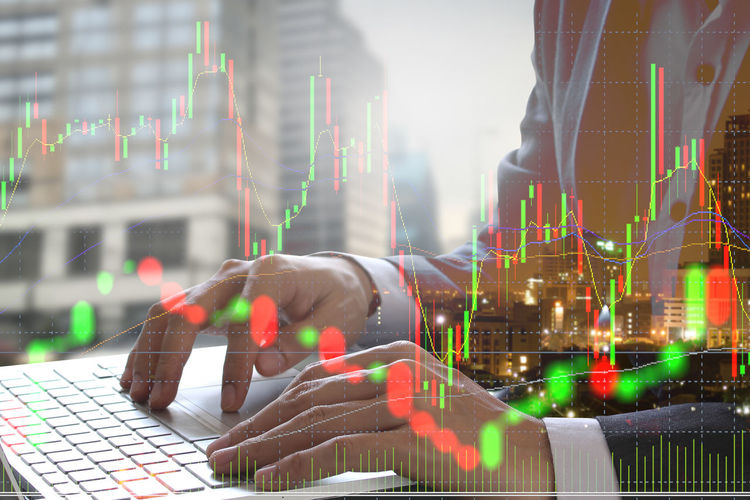 Digital bar graphs against businessman working on laptop at office