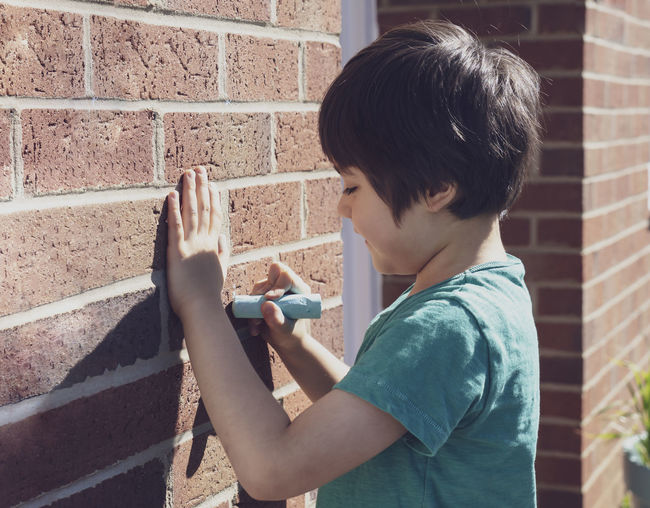Side view of smiling boy writing on brick wall