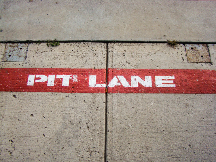 Quick Stop Pit Lane written on floor on Race Tracks Pit Stop Close-up Day No People Outdoors Pit Lane Pitlane Red Text Textured  Western Script Rethink Things Formel 1 Formel One Racetrack Formula 1