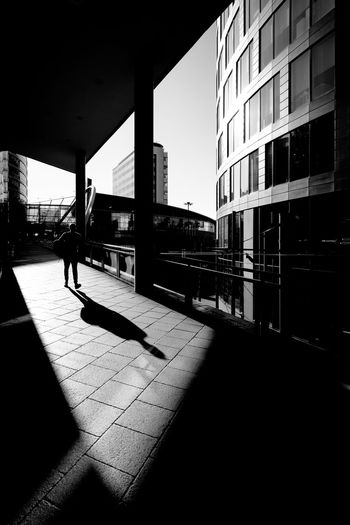 Man walking by building in city against sky