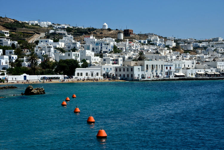 panoramic seaside view of Mykonos with white buildings and moored boat Building Exterior Water Architecture Built Structure City Sea Nautical Vessel Sky Transportation Nature Building Day Travel Destinations Waterfront Town Residential District Land Clear Sky No People Outdoors TOWNSCAPE Mykonos,Greece Marina Seaside View Mooring Greek Architecture Cityscape High Angle View Panorama Travel Summertime Scenics