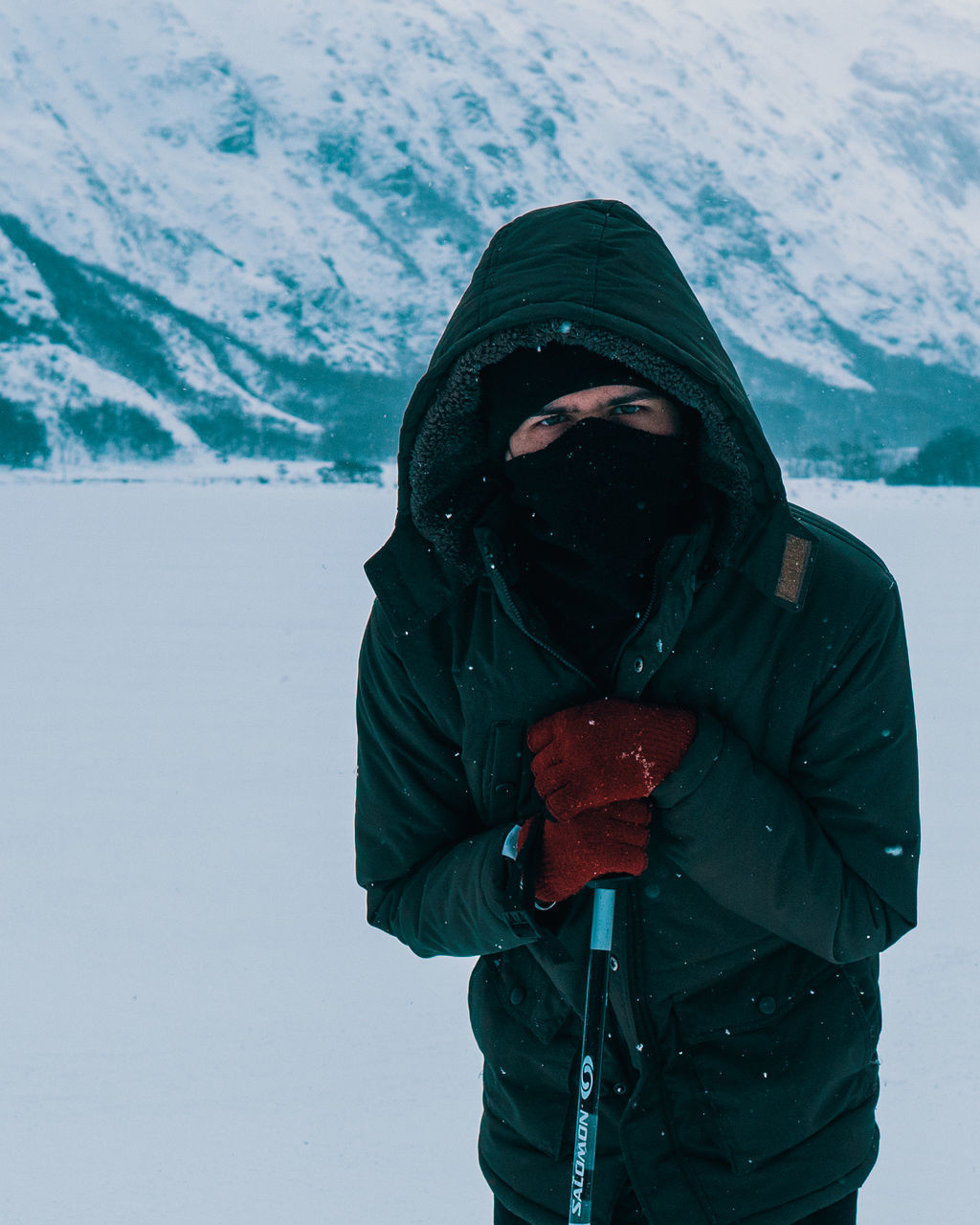 WOMAN WITH UMBRELLA STANDING ON SNOW COVERED MOUNTAIN