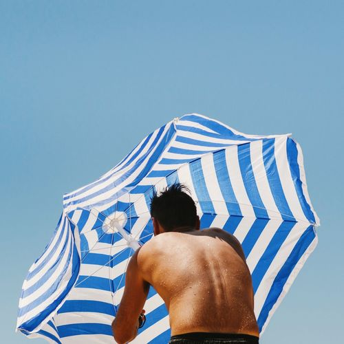 Low Angle View Of Person Holding Beach Umbrella Against Clear Blue Sky