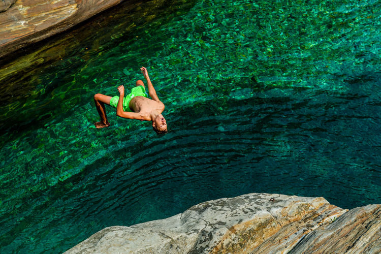 High angle view of shirtless man jumping on rock