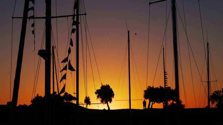 Silhouette sailboats mast against sky during sunset at st martin de re