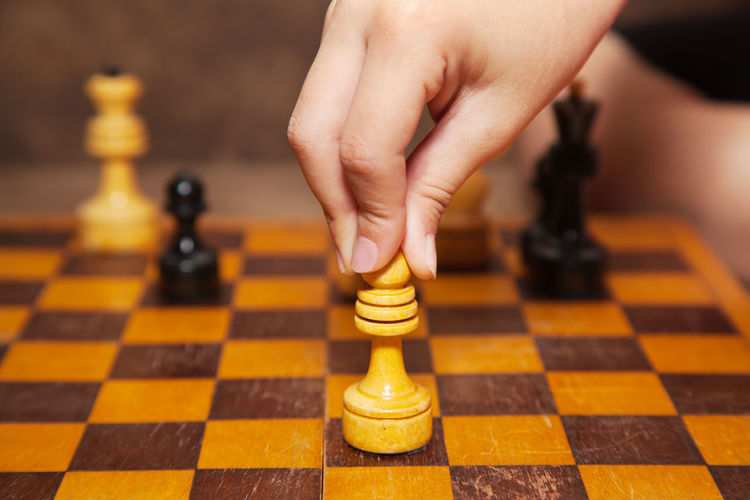 Close-Up Of Cropped Person Playing Chess At Home