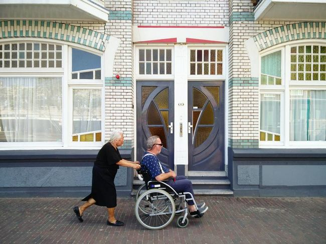 Two People Wheelchair Differing Abilities Architecture Togetherness City vlissingen zeeland Physical Impairment Window Full Length Building Exterior People Day Adult Adults Only Sitting Built Structure Outdoors Wheelchair Access Young Adult Community Outreach