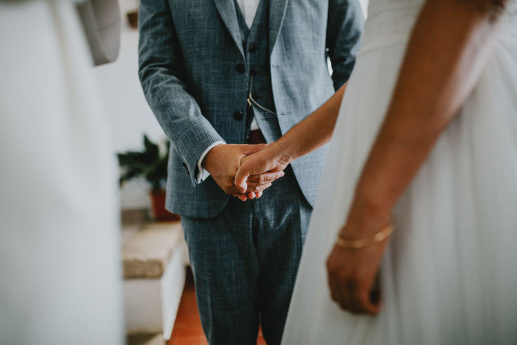 Midsection of couple holding hands during wedding ceremony