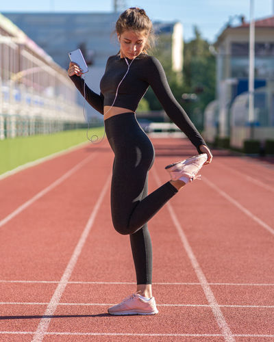 Full length of woman listening music while standing on running track