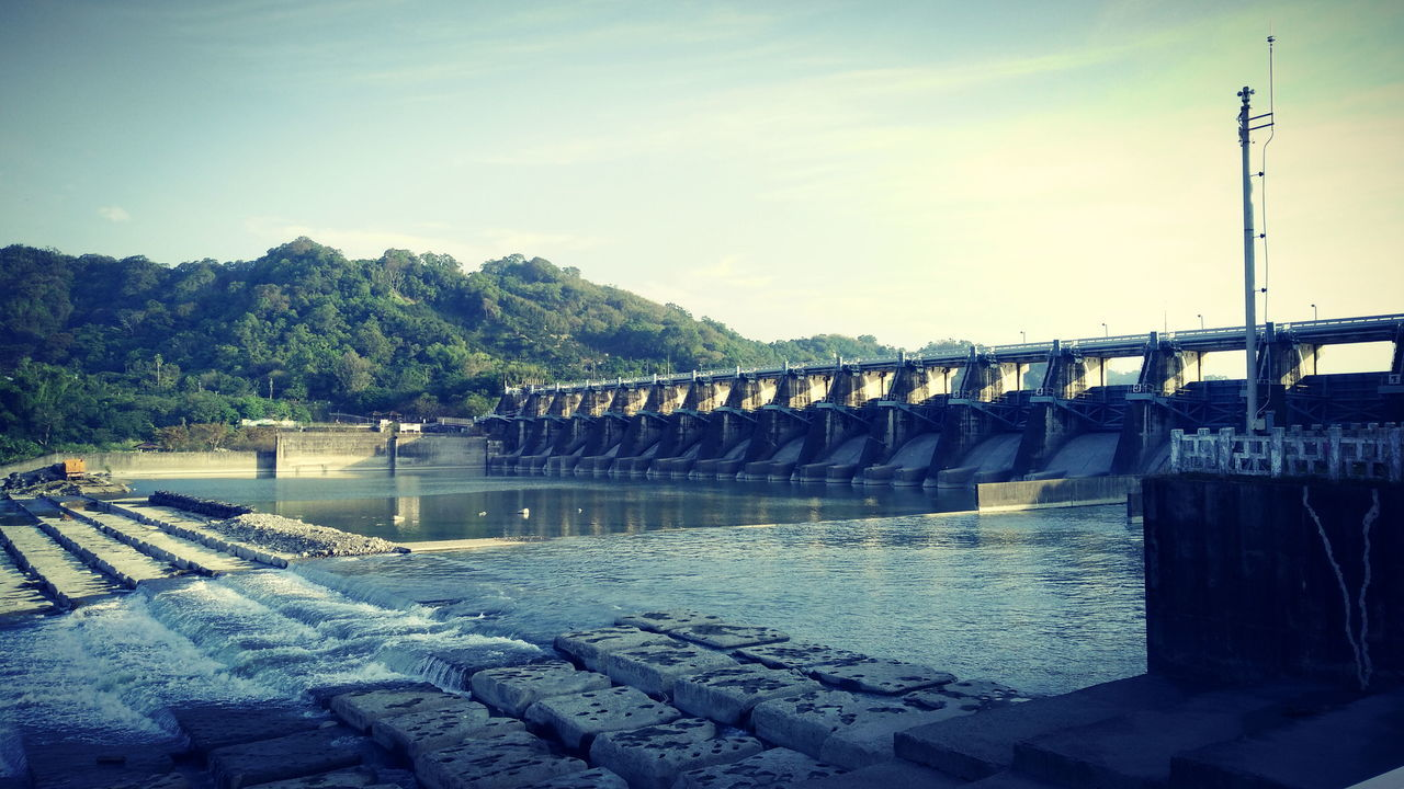 water, river, fuel and power generation, dam, hydroelectric power, connection, bridge - man made structure, renewable energy, no people, architecture, outdoors, built structure, nature, day, sky, alternative energy, power station, industry, tree, beauty in nature