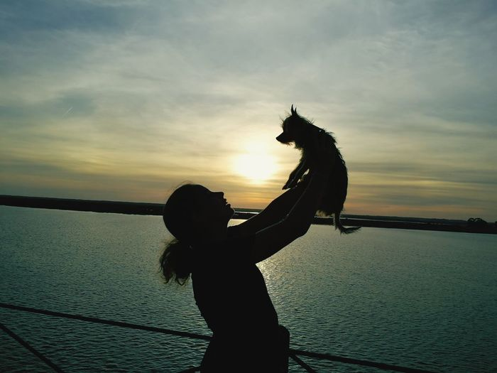 Side view silhouette woman holding dog by sea against sky during sunset
