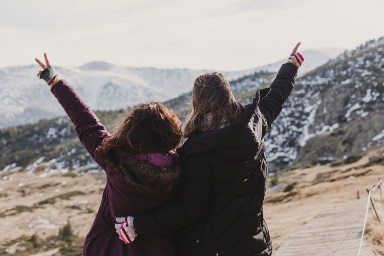 Rear view of female friends with arms raised standing against mountains