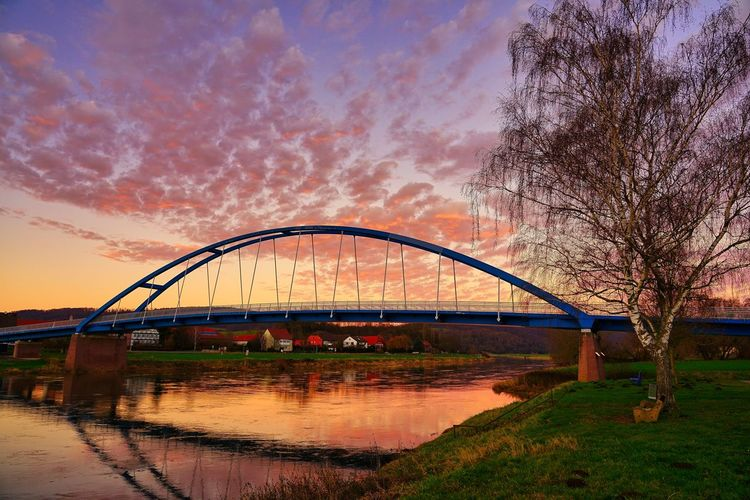 Arch bridge over river against sky during sunset