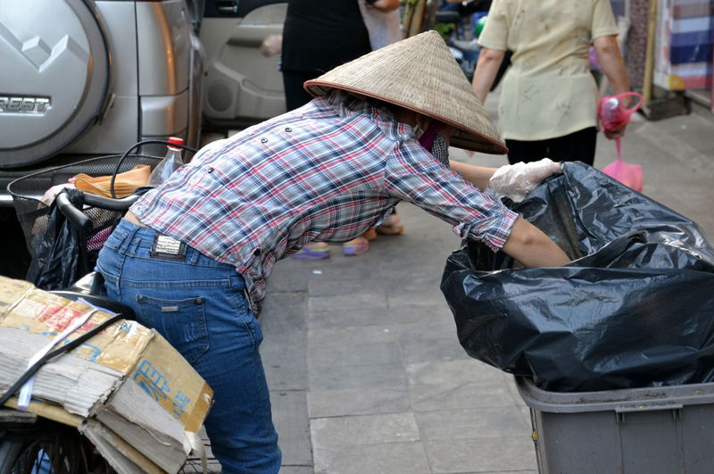 Woman putting waste in garbage can